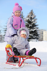 Baby dressed in warm clothes sits on sled and little sister
