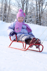 Happy little girl in pink scarf and hat goes tobogganing on snow