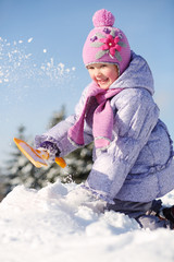 Smiling little girl dressed in warm clothes throws snow