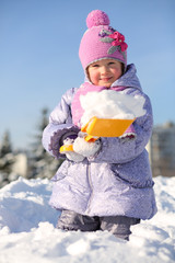 Smiling little girl with shovel shows snow in snowdrift