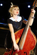 Beautiful woman in black dress plays old contrabass