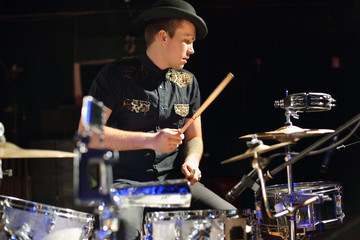 man in hat and black shirt plays drum set in night club