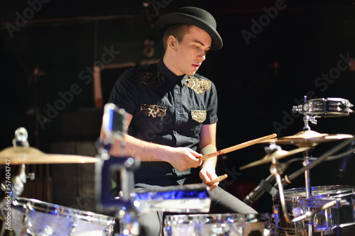 man in hat plays drum set in night club.