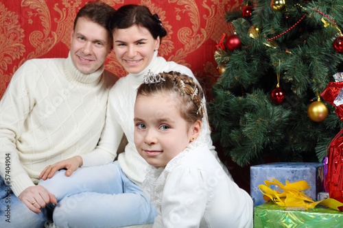 Family sit with gifts near Christmas tree at home.