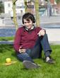 junger mann hört im park musik