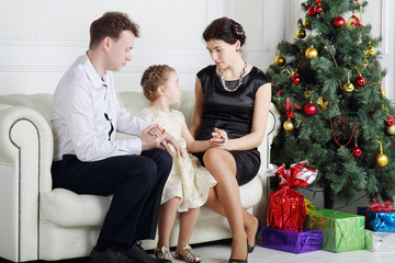 Father and mother talk with daughter on sofa near Christmas tree