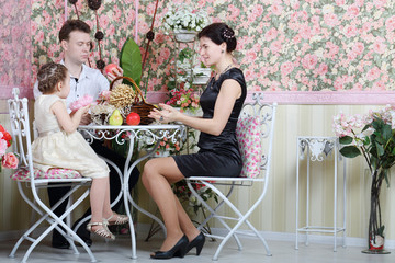 Father, mother and  daughter sit at table with fruits
