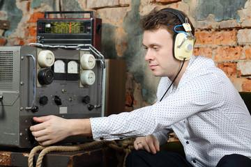 Man in headphones configures power source to radio receive