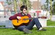 junger mann spielt draußen gitarre