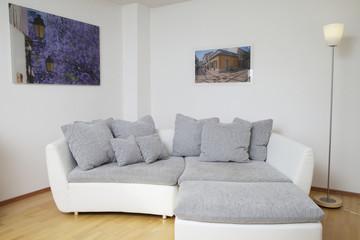 Modernes Sofa mit Hocker und vielen Kissen