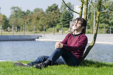 junger mann relaxt im park