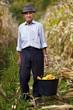 Old farmer holding a bucket full of corn cob