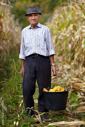 Old farmer holding a bucket full of corn cob