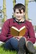 junger mann liest im park