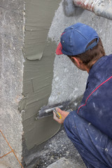 building worker spreading mortar on concrete wall 2