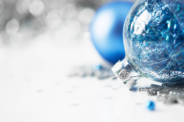 Blue and silver xmas ornaments on bright holiday background