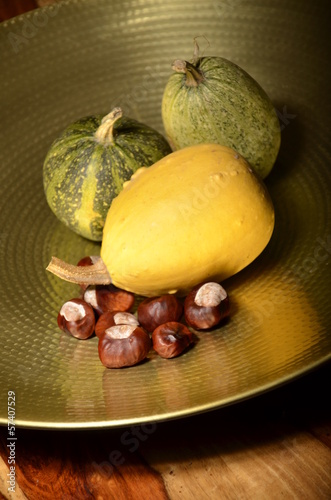 still life made of three pumpkins and chestnuts