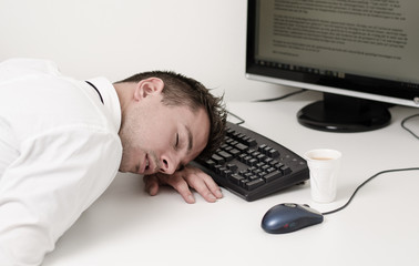 tired businessman sleeping on computer