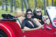 women at retro car with dark glasses