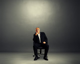 pensive businessman sitting on office chair