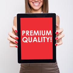Cute businesswoman showing tablet that states premium quality