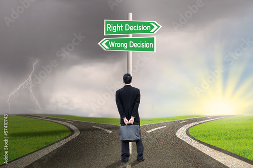 Businessman looking at sign of right vs wrong decision