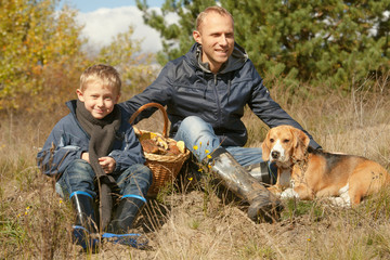 Father with son and pet resting on the forest glade