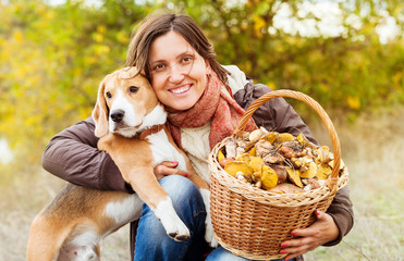 Pretty woman with her favorite pet in autumn forest