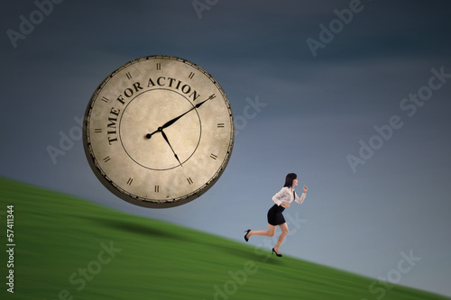 Businesswoman running with a big time clock on hill