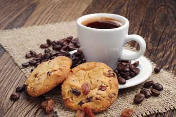 Cup of coffee and cookies with raisins