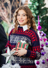 Woman Holding Christmas Present In Store
