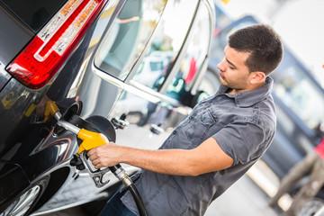 Young Man Filling His Car at Gas Station