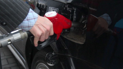 Businessman pulls out gasoline pistol fueling car petrol station