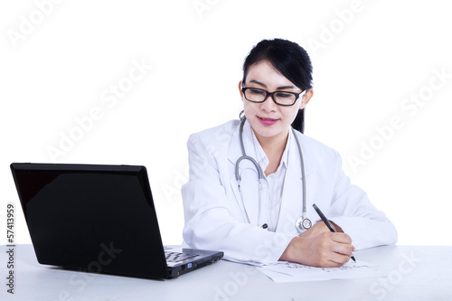 Young female doctor is writing prescription