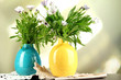 Bouquet of beautiful summer flowers in color vases,
