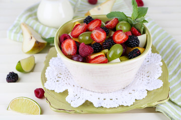 Fruit salad in plates on wooden table near napkin