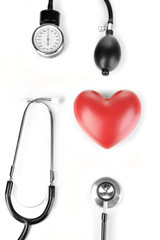 Tonometer, stethoscope and heart isolated on white
