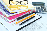 Office supplies with glasses and documents close up