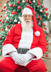 Santa Claus Sitting Against Christmas Tree