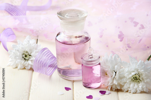 Glass bottle with color essence, on wooden background
