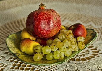 autumn grape, apple, pomegranate fruits in bowl