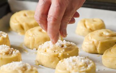 A senior sprinkling sugar over sweet rolls