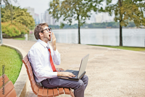 businessman yawning on a park bench