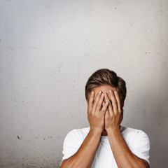 young man hiding his face
