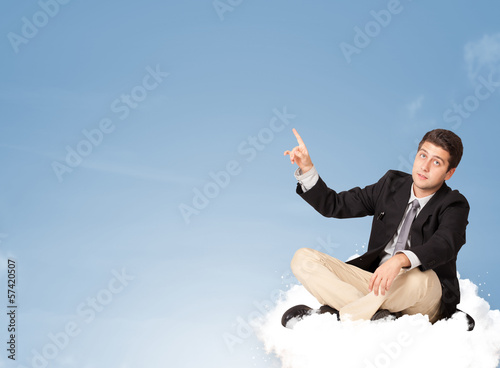 Attractive businessman sitting on cloud with copy space