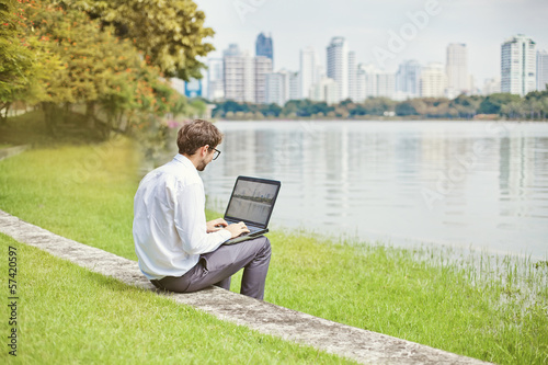 man with laptop in park of megapolice