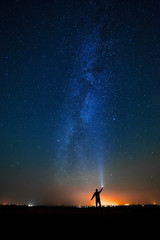 The man on the background of bright stars of the night sky. The