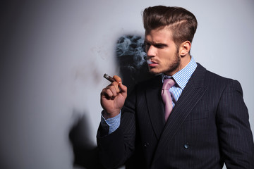 fashion model in suit and tie enjoying his cigar