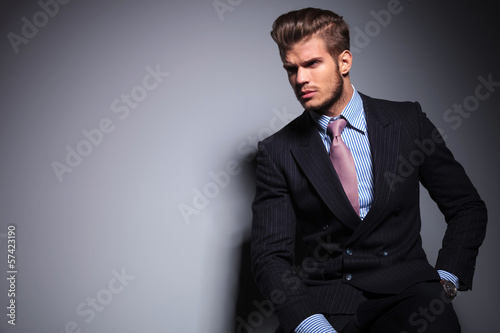 seated young fashion model in suit looks away