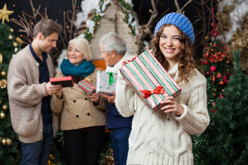 Woman Holding Christmas Present With Family In Background